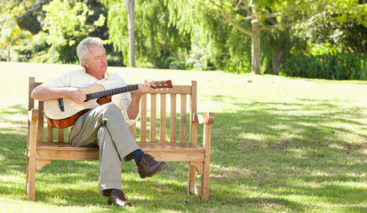 Man playing a guitar as he sits with his legs crossed