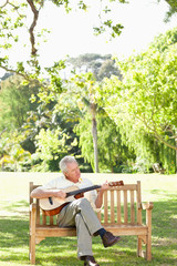 Man playing a guitar with his eyes closed as he sits on a bench