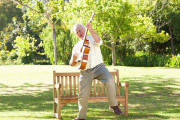 Man standing in front of a bench while playing a guitar