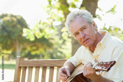 Man looking to his side while playing the guitar