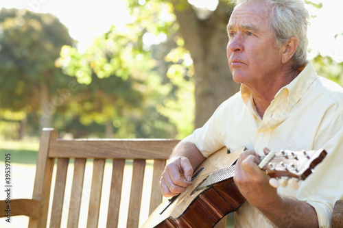 Man looking ahead while playing the guitar on a bench