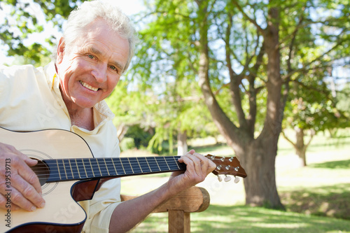 Man smiling while playing a guitar while sitting on a bench with a tree in the back