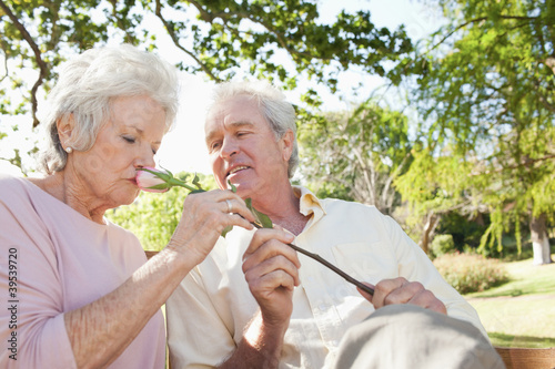 Woman closely smells a flower which is being held by her friend