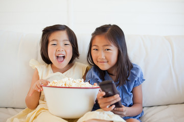 Two sisters on the couch with a bowl of popcorn and the tv remote while laughing