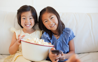 Sisters smiling on the sofa while watching tv and  laughing as they enjoy popcorn