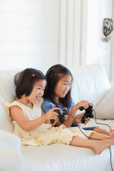 Two sisters playing games together on the couch