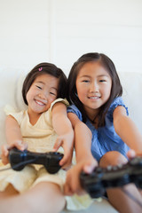 Close up of two sisters with controllers in their hands while playing a game