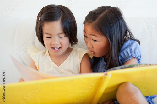 One sister turning the page as the other still reads
