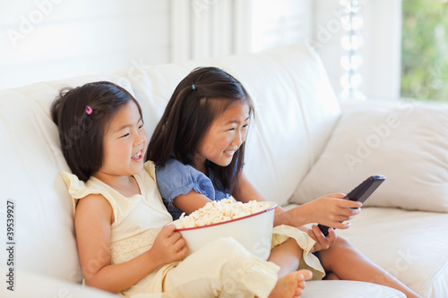 Side view of two sisters laughing while watching tv on the couch
