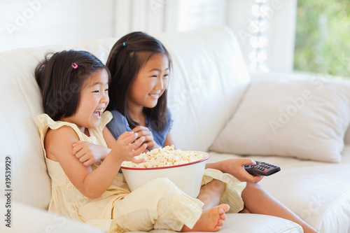 Side view of two sisters watching tv and eating popcorn
