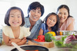 Close up of a smiling family about to prepare a salad in the kitchen