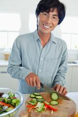 Smiling father prepares a salad