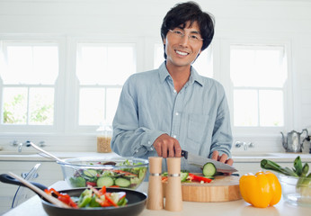 Man smiles as he prepares a salad in the kitchen
