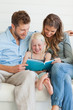 Smiling girl sitting in between parents as they all read a book