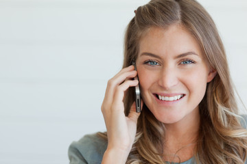 Close up of a woman on her mobile looking ahead and smiling