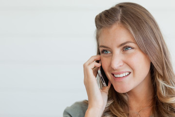 Close up of a woman on her phone chatting and smiling