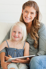 The mother holds a tablet pc in front of the young girl
