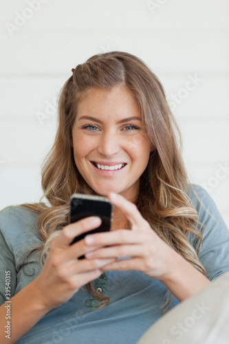 A woman smiling while using her mobile to send a text and looking forward