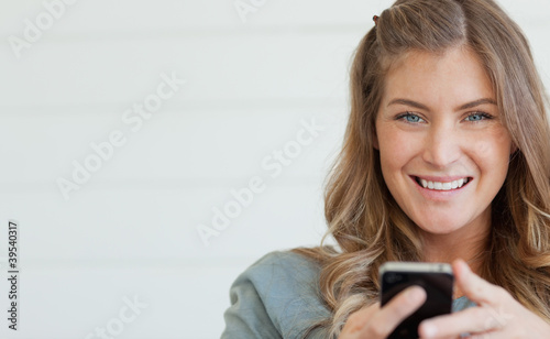 A woman smiling and looking straight ahead as she holds her phone