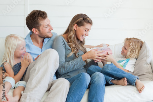 A happy family sit on the couch as the son hands his mother a present