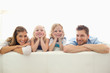 Smiling family on the back of the couch with their arms folded and raised