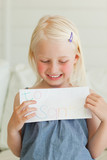 A smiling girl with a letter to go to santa