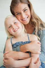 Close up of a smiling mother and daughter as they look ahead with their heads tilted