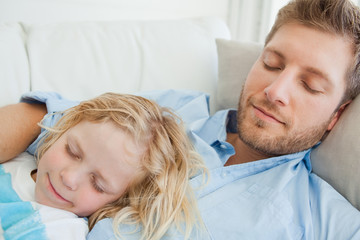 Close up of a boy and his father asleep on the couch