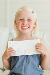 A smiling child with a letter to Santa