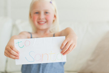 A girl holding her letter out addressed to Santa