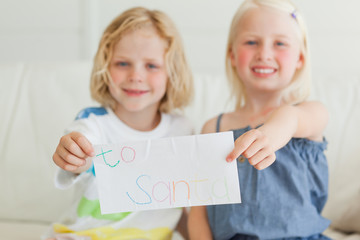 A letter to Santa being held by a brother and sister