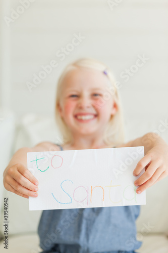 A smiling girl holding a letter to Santa