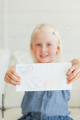 Focus on the letter to Santa as a girl holds it