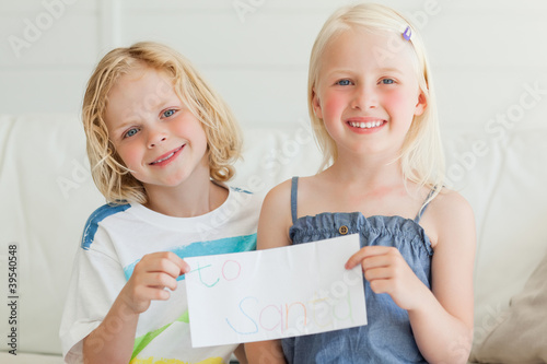 A boy and girl smile as they hold a letter to Santa