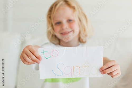 A young boy holding a letter to santa