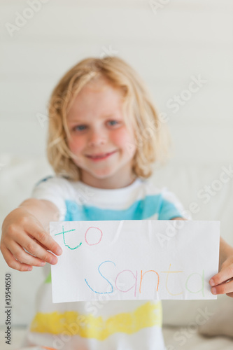 A small boy smiling as he holds a letter to santa