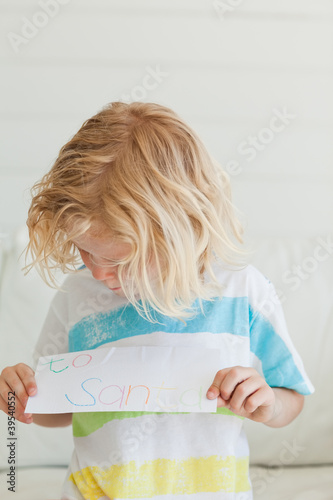 A young boy looking at his letter to santa