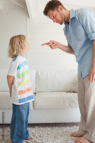 A father pointing to his son as he corrects him for doing something bad