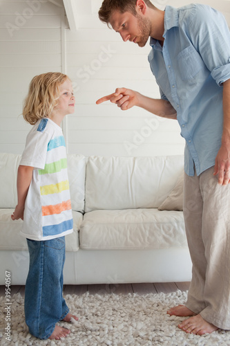 A father points at his son with a look of anger as the boy smiles