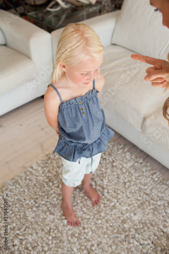 A child looks to the floor as she is upset as her mother gives out