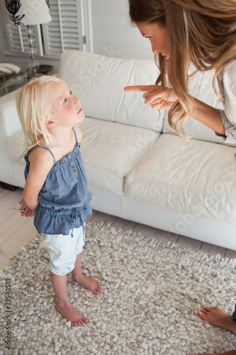 A scolded child looks up to her mother as she is being punished