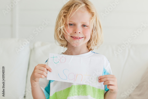 A smiling boy holds up his letter to santa