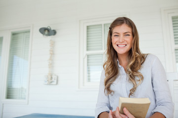 A smiling woman sits on the porch with a book in her hands