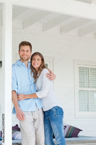 A man and woman looking up and smiling while standing outside