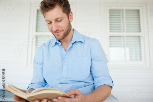 A smiling man sits on the porch while reading a book