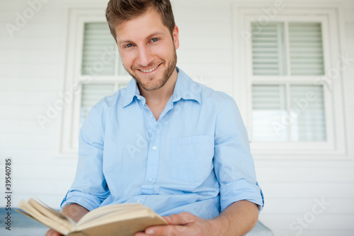 A smiling man takes a break from the book for a moment