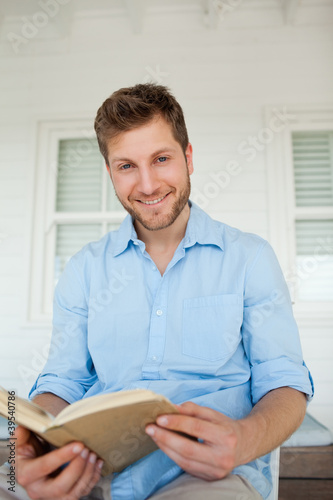 A man with an open book in his hands smiles