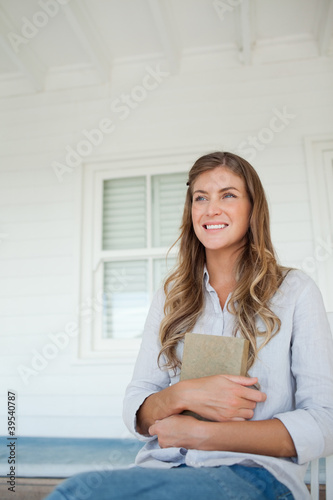 A smiling woman holds a book to her chest