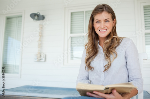 A smiling woman with her book in her hands