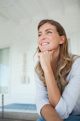 Woman looks up with her hand on her chin